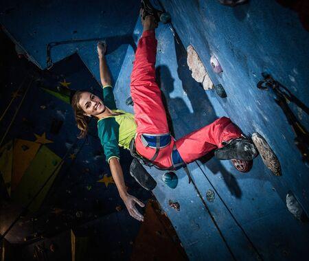 젊은 여자 실내 바위 벽에 암벽 등반 연습