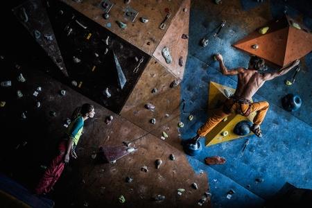 Muskulöser Mann üben Klettern an einer Felswand im Innenbereich