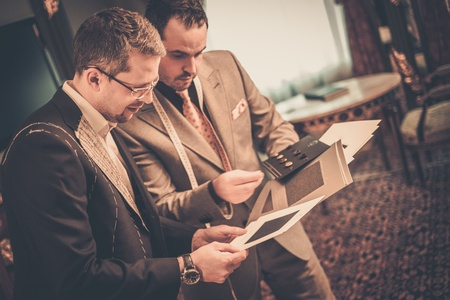Tailor and client choosing cloth and buttons for custom made suit Reklamní fotografie