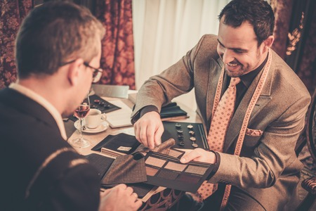 Tailor and client choosing cloth and buttons for custom made suit Standard-Bild