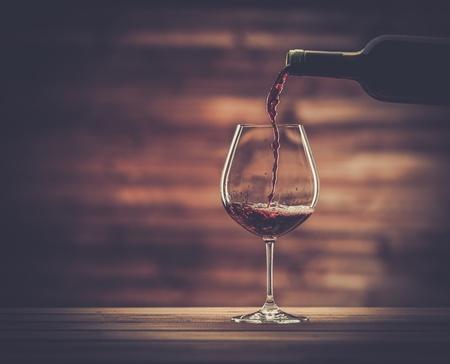 Verter el vino tinto en el vaso contra el fondo de madera Foto de archivo