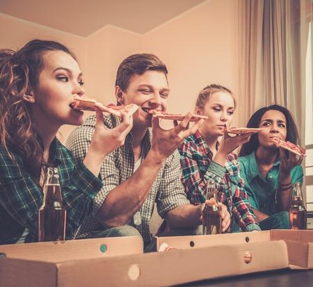 Groep jonge multi-etnische vrienden met pizza en flessen drank vieren in interieur Stockfoto - 33956351