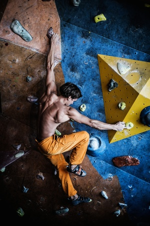 Muscular man practicing rock-climbing on a rock wall indoors 免版税图像