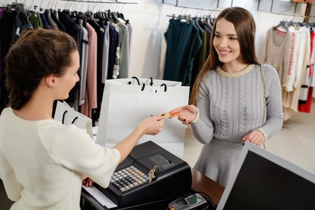 Happy woman customer paying with credit card in fashion showroom Zdjęcie Seryjne