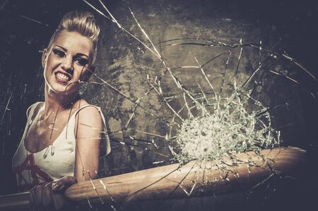 Punk girl breaking glass with a baseball bat Stock Photo