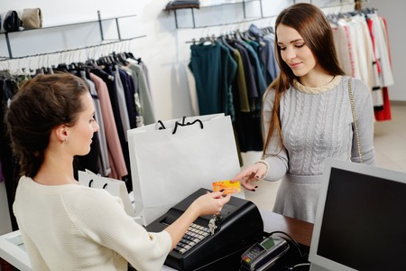 Happy woman customer paying with credit card in fashion showroom Foto de archivo