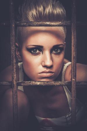 Troubled tiener meisje achter de tralies Stockfoto