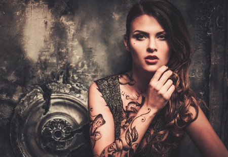 古い不気味なインテリアで刺青の美しい女性