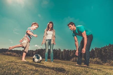 幸せな若い家族屋外サッカー