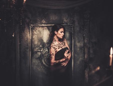 古い不気味なインテリアで美しい女性の入れ墨