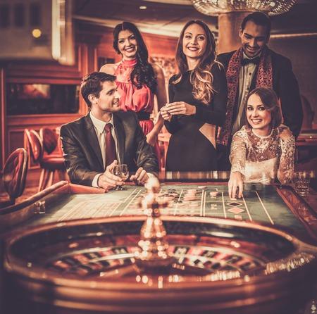 Groep van stijlvolle mensen die het spelen in een casino Stockfoto
