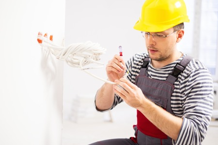 Electrician working with wires in new apartment Stock fotó