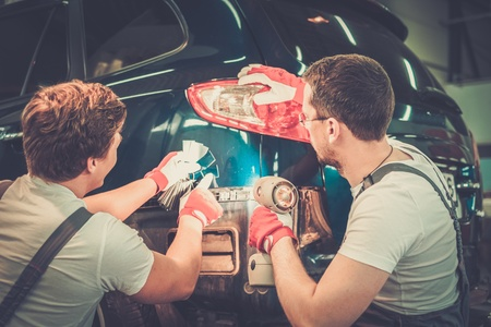 車のボディ ・ ワーク ショップの色合いが、正しい選択色サンプルと 2 人の労働者 写真素材