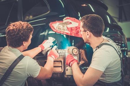 Dos trabajadores con muestras de color que eligen tono correcto en un taller de carrocería del coche Foto de archivo - 35023140