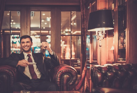 豪華なインテリアでコーヒーのカップと座っているハンサムな笑みを浮かべて男 写真素材