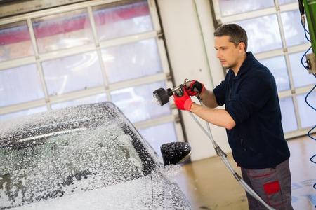 Mensenarbeider wassen luxe auto op een wasstraat Stockfoto