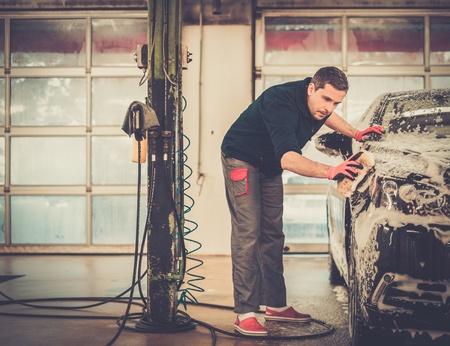 Mensenarbeider wassen luxe auto met spons op een wasstraat