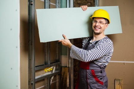 Builder with plasterboard in new building interior Stockfoto