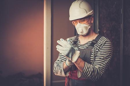 Bouwer in beschermende kleding tijdens de nieuwbouw
