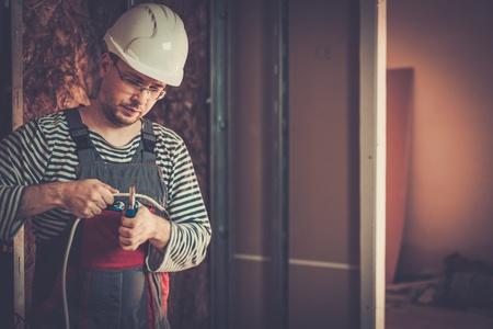 Elektricien werken met draden in nieuw appartement Stockfoto