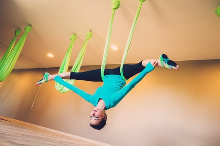 young woman performing antigravity yoga exercise photo athletic woman lying arms crossed inside orange aerial yoga      rh   123rf
