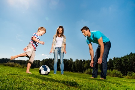 Gelukkig jong gezin voetballen buitenshuis Stockfoto