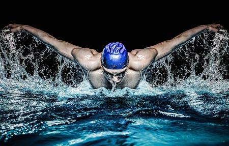 スイミング プールの青い帽子の筋肉の若い男