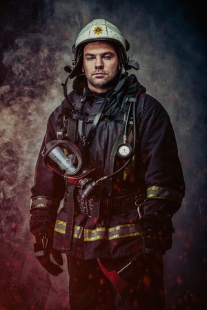 Firefighter with helmet and axe in a smoke Archivio Fotografico
