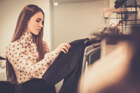 Jonge vrouw het kiezen van kleding op een rek in een showroom Stockfoto