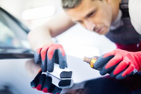 Werknemer op een auto wassen aanbrengen van nano-coating op een motorkap Stockfoto