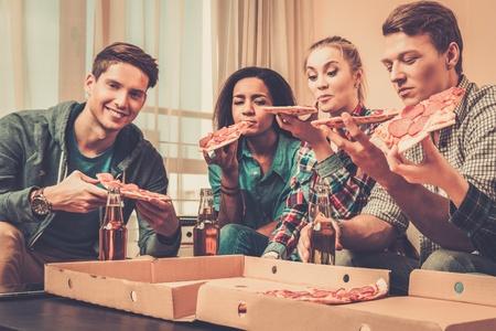 Groep van multi-etnische vrienden met pizza en flessen drank die partij hebben Stockfoto - 35510308