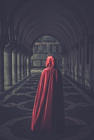 Donna in mantello rosso si allontana Archivio Fotografico - 36043548
