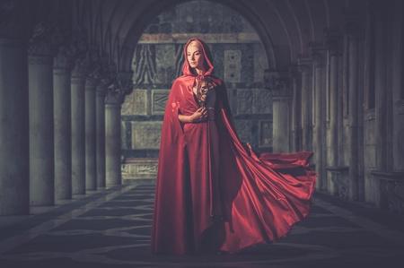 Donna con una maschera che indossa all'aperto mantello rosso Archivio Fotografico - 36043626