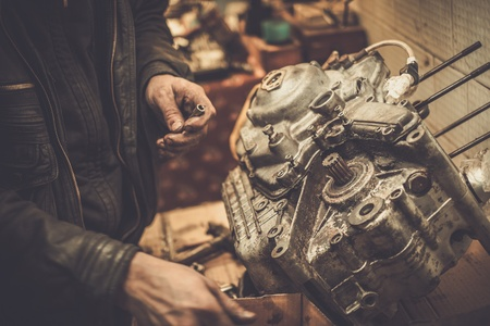 Mechanic working with with motorcycle engine in a workshop Standard-Bild