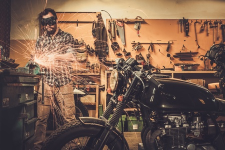 Mechanic doing lathe works in motorcycle customs garage Imagens