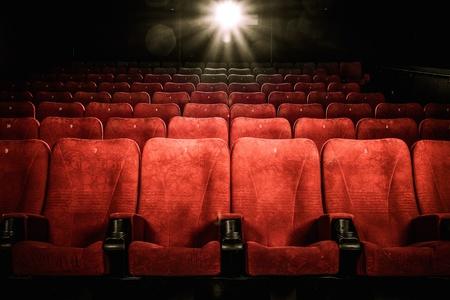 Lege comfortabele rode stoelen met nummers in de bioscoop