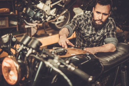 Mechanic building vintage style cafe-racer motorcycle  in custom garage Stock Photo