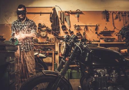 Mechanic doing lathe works in motorcycle customs garage Stock Photo