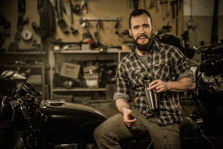 ライダーとビンテージ スタイル カフェ レーサー バイクの彼の習慣に