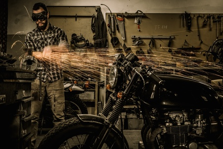 Mechanic doing lathe works in motorcycle customs garage Stock Photo