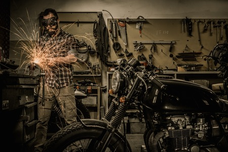 Mechanic doing lathe works in motorcycle customs garage Stok Fotoğraf
