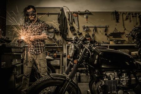 Mechanic doing lathe works in motorcycle customs garage Stockfoto