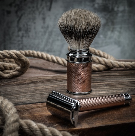 Veiligheid scheermes en scheerkwast op een houten achtergrond Stockfoto