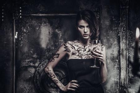 Tattooed beautiful woman in old spooky interior