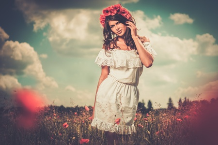 Beautiful girl wearing white summer dress and flower chaplet in poppy filed Stock Photo