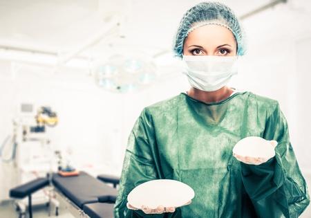 手術室内で異なるサイズのシリコン乳房インプラントを保持している形成外科医女性