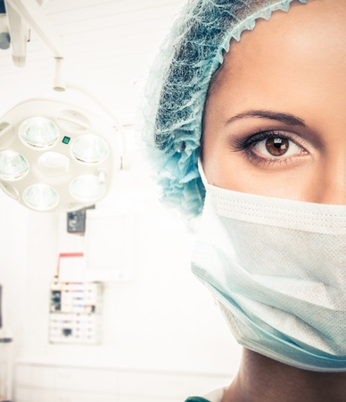 Young woman doctor in cap and face mask in surgery room interior