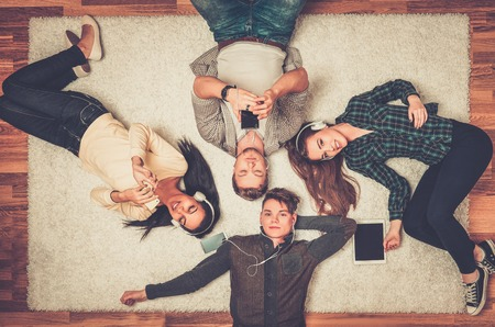 Happy multiracial friends relaxing on a carpet with gadgets Banque d'images