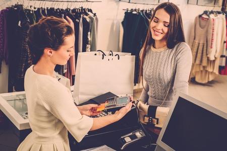 幸せな女顧客のファッションのショールームでクレジット カードで支払い