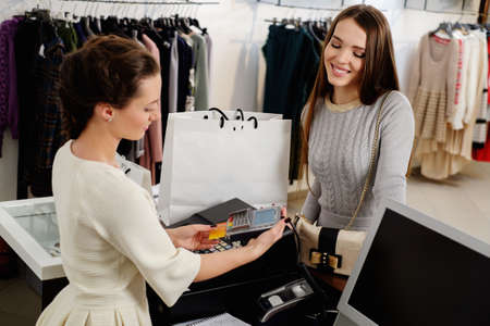 Happy woman customer paying with credit card in fashion showroom 스톡 콘텐츠